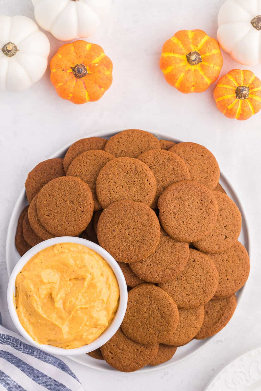 a plate of ginger cookies with pumpkin pie dip