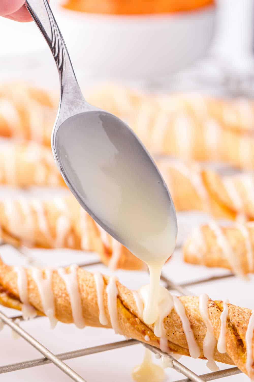 a spoon drizzling glaze on an air fryer pumpkin pie twist