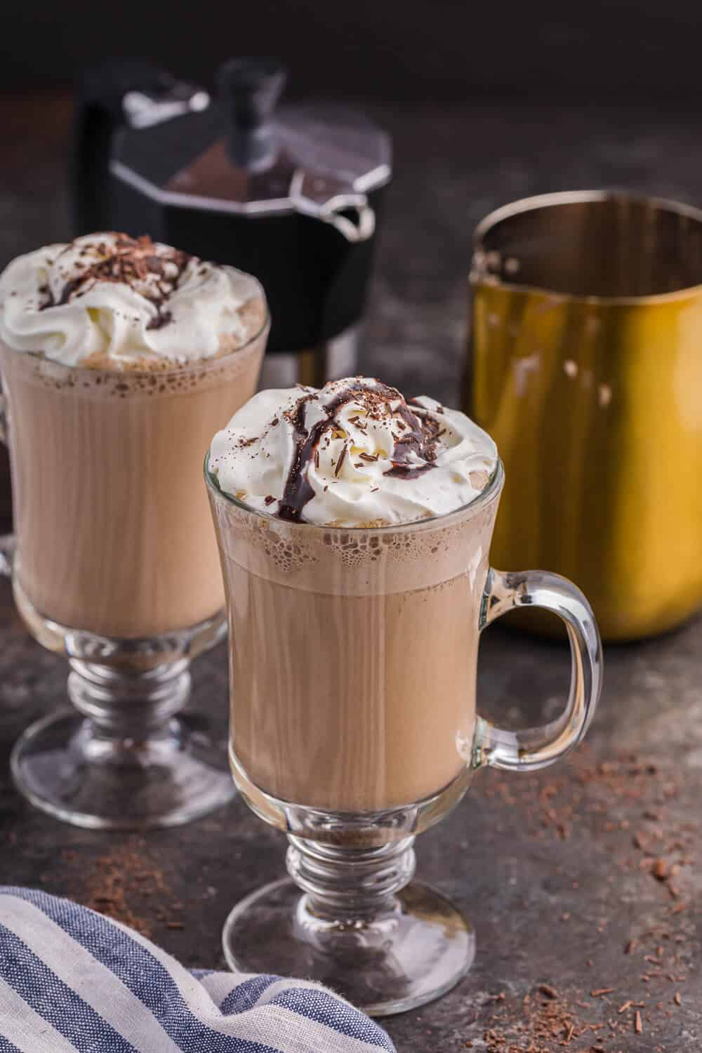 two mugs of mocha latte with an espresso maker and a milk frothing pitcher