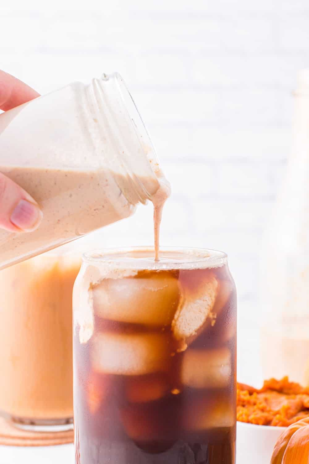 pumpkin spice creamer being poured into iced coffee