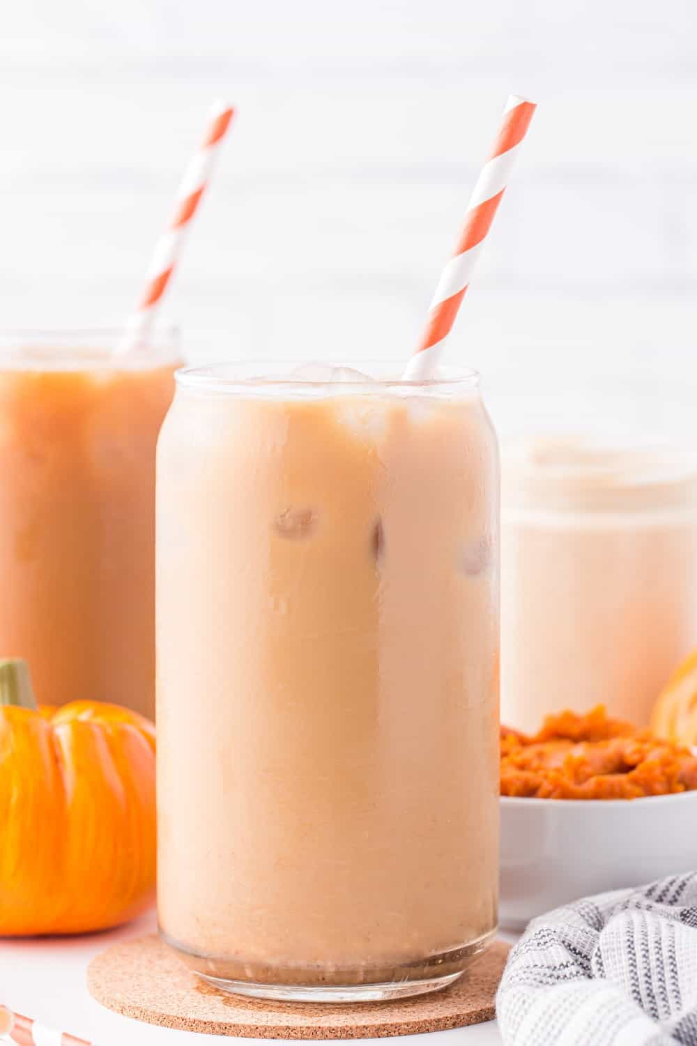 iced coffee with pumpkin spice creamer in a glass jar with a straw