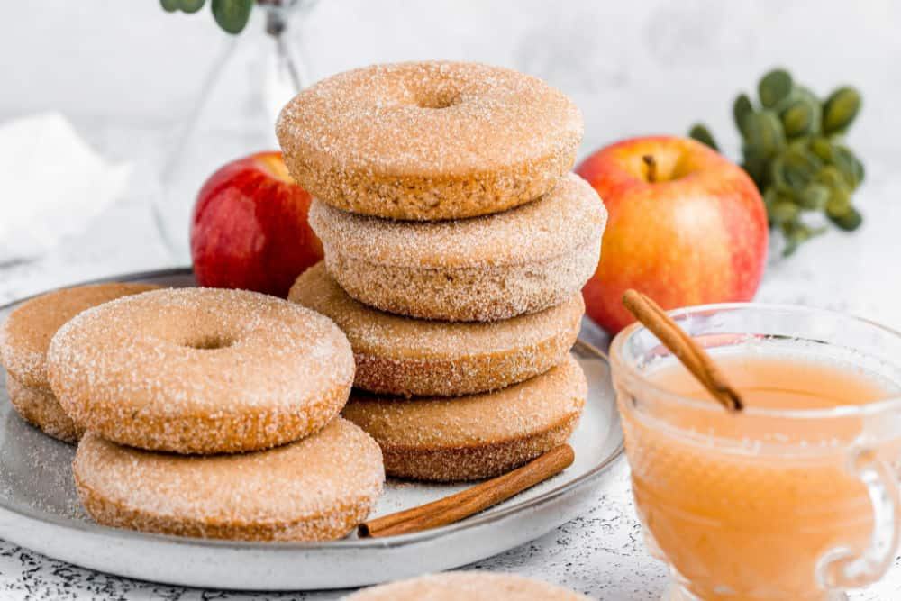 baked apple cider donuts stacked on a plate