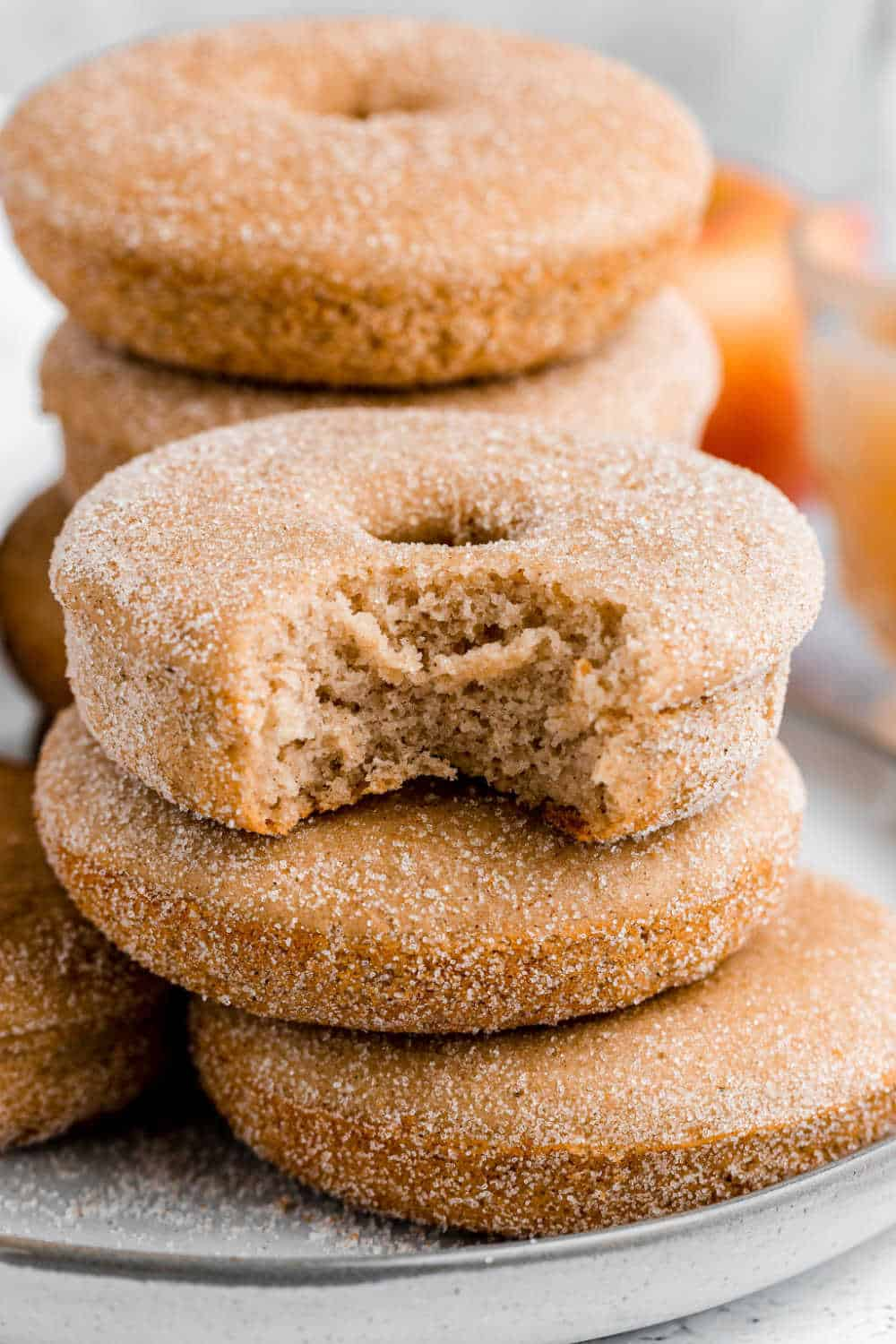 baked apple cider donuts stacked on a plate with a bite out of one